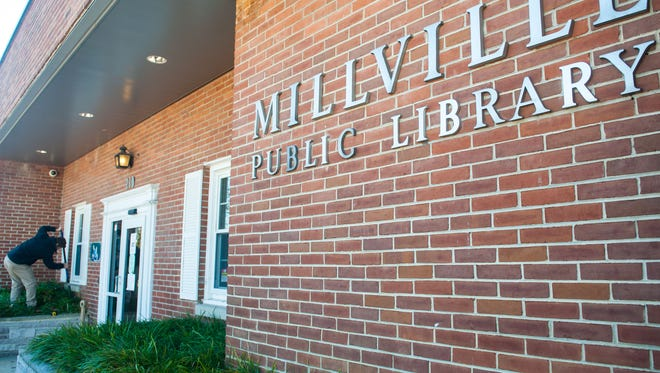 Scott Edelstein begins digging up a flower bed at the Millville Public Library on Tuesday, October 31.