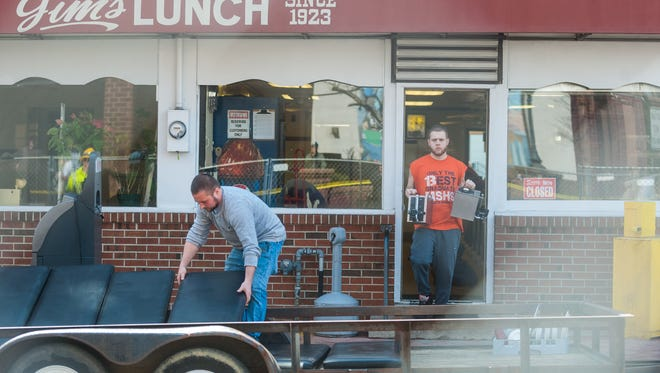 Workers remove belongings from Jim's Lunch on Thursday, March 29.