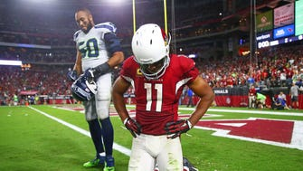 Arizona Cardinals wide receiver Larry Fitzgerald (11) and Seattle Seahawks linebacker K.J. Wright (50) react following the game at University of Phoenix Stadium.