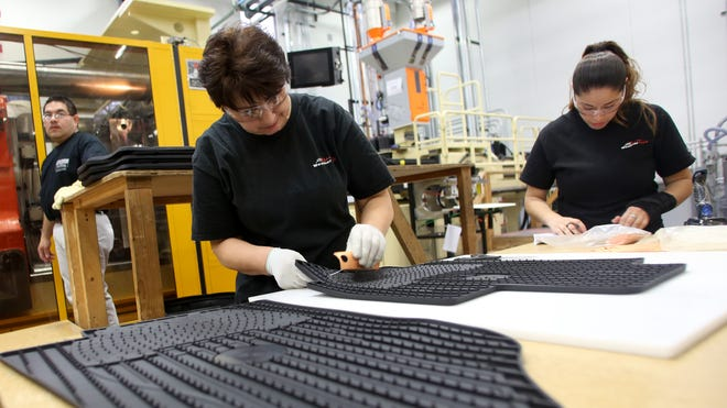 MacNeil Automotive Products employees Zofia Stachowicz, left, and Karina Rodriguez prepare WeatherTech floor mats for packaging in the manufacturing facility at the company's headquarters in Bolingbrook, Ill.,  on Feb. 5, 2014.