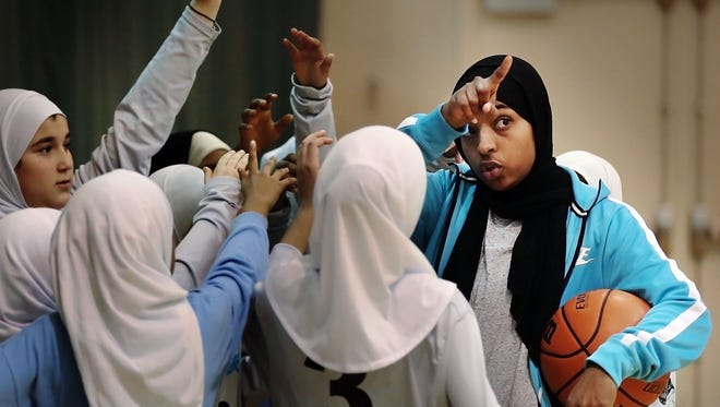 """Bilqis """"Qisi"""" Abdul-Qaadir (right), athletic director at Pleasant View School and former Lady Tigers basketball player, gives her girls basketball team some final instructions before they play a game against the Germantown Grizzlies at Independent Presbyterian Church."""