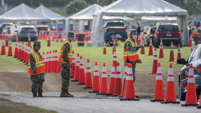 National Guard soldiers direct people on where to go as they drive through the COVID-19 testing site Tuesday at the FITTEAM Ballpark of The Palm Beaches in West Palm Beach.
