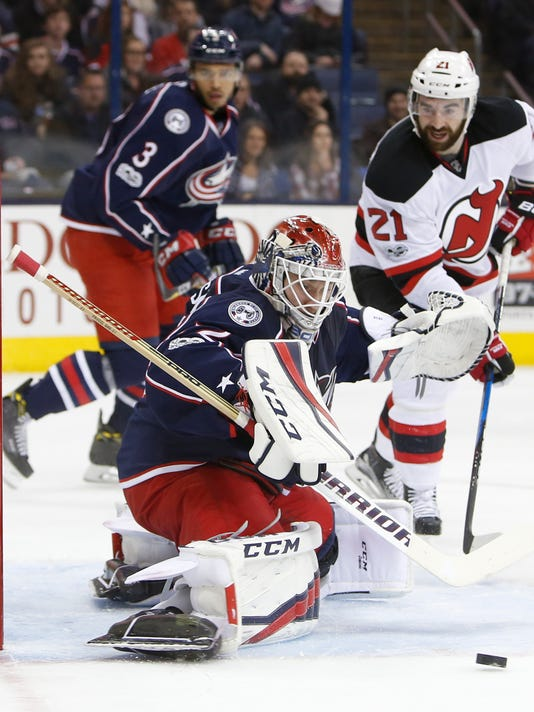 Columbus Blue Jackets' Sergei Bobrovsky, front, of Russia, makes a save against New Jersey Devils' Kyle Palmieri during the first period of an NHL hockey game Saturday, Feb. 4, 2017, in Columbus, Ohio. (AP Photo/Jay LaPrete)