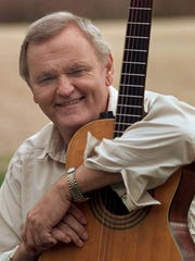 Jerry Reed poses with his guitar during an interview