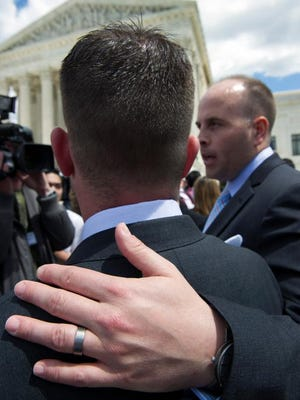 Plaintiffs Thomas Kostura, left, and his husband Ijpe Dekoe of Memphis speak with reporters Tuesday outside the Supreme Court in Washington after sitting in on gay marriage arguments at the court.