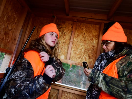 Taylor Howell, left, and her grandmother Cheryl Howell prepare to leave their blind after Taylor shot a deer on her grandparents' property in Fawn Township.