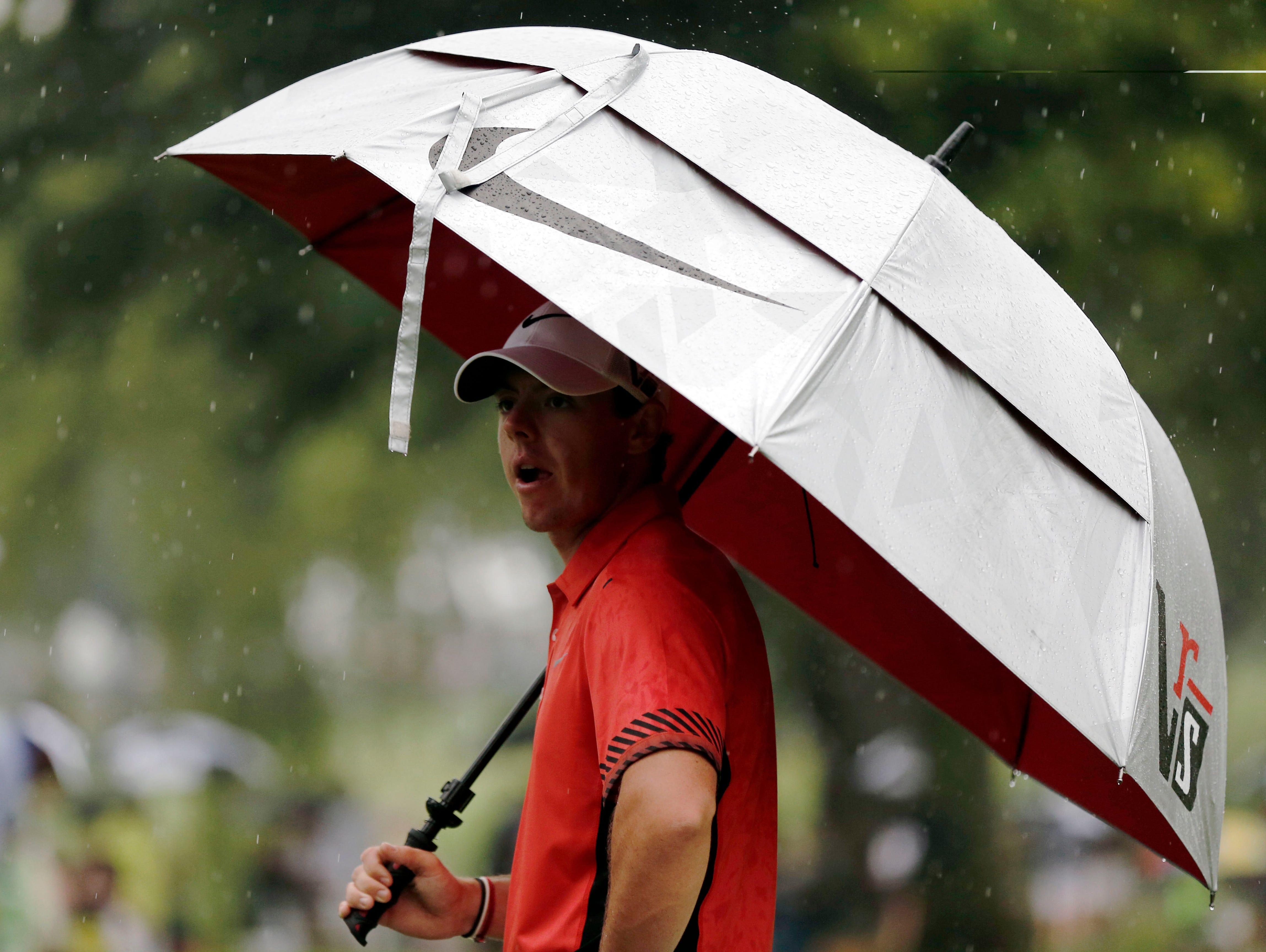 Rory McIlroy tries to stay dry before the start of the second round.