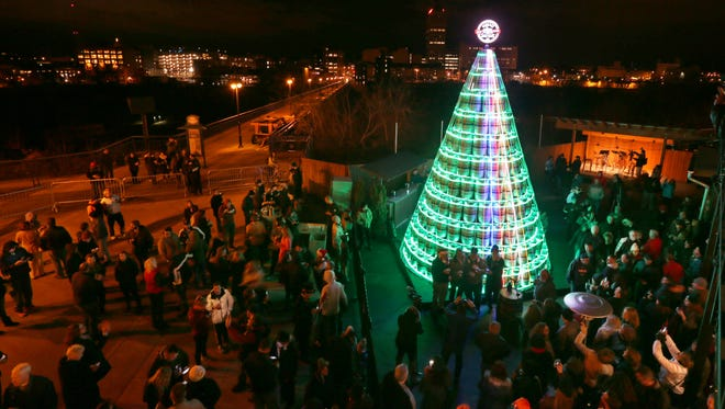 Hundreds gather around as the lights are turned on the 26 foot high Keg Tree at the Genesee Brewery's 3rd annual tree lighting ceremony Friday, Dec. 2, 2016 in Rochester.