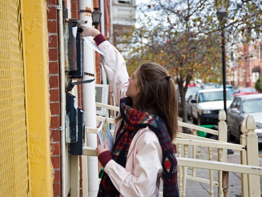 Veronica Smith places a flier in a mailbox along East Philadelphia Street in York. She and 11 other children were handing out fliers for the First Presbyterian Church of York's free Thanksgiving dinner on Wednesday.