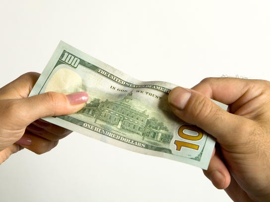 A man's hand and a woman's hand hold a hundred-dollar bill.