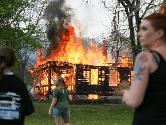 Bystanders watch as a vacant home on Old Baltimore Pike used for training by the Christiana Fire Company is allowed to be consumed by fire Saturday.