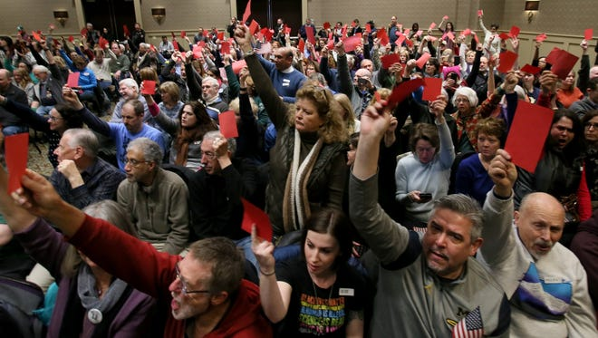 By showing red cards, people showed off and voiced their displeasure or opposition to answers to various questions by U.S. Representative Dave Trott during his public town hall last month at the Suburban Collection Showplace in Novi. More than 450 people attended the event in a small ballroom inside.