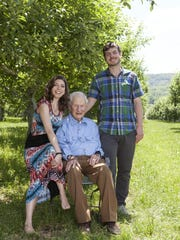 Robert Morgenthau shares a shady spot with his two youngest children, Amy and Josh, under an apple tree at the family's Fishkill Farms' orchard in Hopewell Junction.