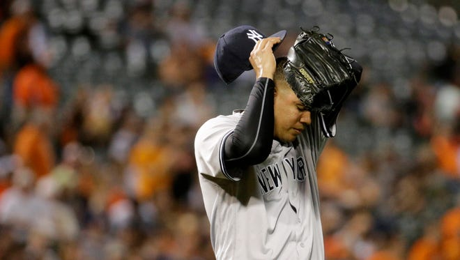 New York Yankees relief pitcher Dellin Betances wipes his face after Baltimore Orioles' Adam Jones scored on a groundout by Manny Machado in the seventh inning of a baseball game in Baltimore, Friday, June 3, 2016. Baltimore won 6-5.
