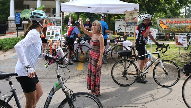 Patty Ankrum of Mount Vernon hands out milkweed seed balls to riders in Mount Vernon during RAGBRAI on July 24. Riders were instructed to toss the seeds in the ditches along the route in hope of helping to recover the lost populations of monarch butterflies.