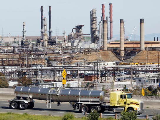 A tanker truck passes an oil refinery in Richmond,