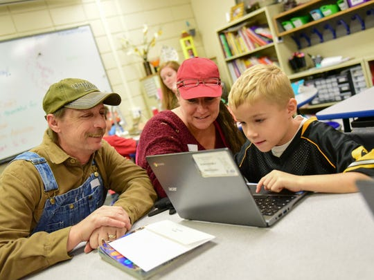Grandparents Jeff and Lori Smith work on the computer with their grandson at Rolling Green Elementary.
