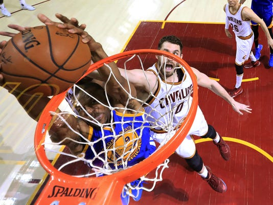 Golden State Warriors forward Andre Iguodala (9) dunks on Cleveland Cavaliers forward Kevin Love (0) during the second half of Game 3 of basketball's NBA Finals in Cleveland, Wednesday, June 7, 2017. Golden State won 118-113. (Ronald Martinez/Pool Photo via AP)