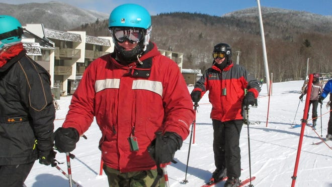 Tyler Arel, who served in the U.S. Air Force from 2006 to 2009, center, waits in a lift line with fellow veterans, who suffer post-traumatic stress disorder, while skiing together at Bolton Valley Resort in Bolton, Vt, Thursday Feb. 18, 2016.  A group of service members of the Gulf, Iraq and Vietnam wars say the weekly gatherings through the Vermont Adaptive Ski & Sport programs help get them out of the house, connect with other people and take their mind off of their post-traumatic symptoms.