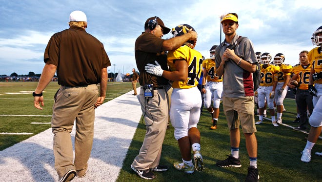 Kickapoo head coach Kurt Thompson embraces running back Malachi Stout (40) after Stout ran for a touchdown during a 2015 win over Parkview.