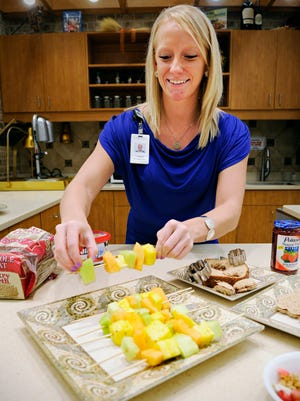 Dani Berg, health and wellness coach from HealthPartners Central Minnesota Clinic, shows some healthy snacks for the summer Tuesday including fruit kabobs, healthy on-the-go trail mix and sandwich cutouts.
