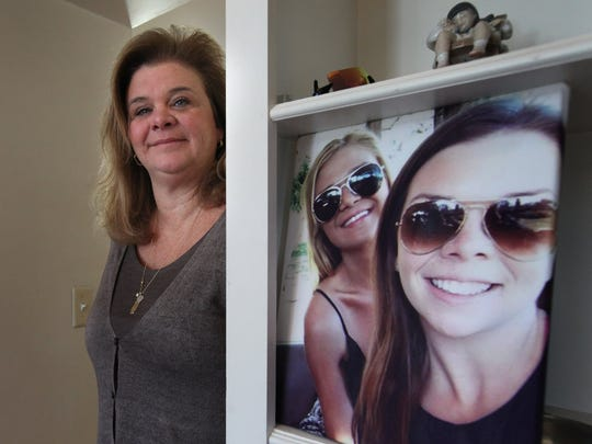 Jennifer Stalker at her home in Grosse Pointe in March 2015. The photo to her left shows daughters Madison and Pagie, who was 16 when she was killed in 2014.
