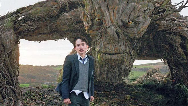 "Conor (Lewis MacDougall) confronts The Monster (performed and voiced by Liam Neeson) in J.A. Bayona's visually spectacular and stunningly emotional drama ""A Monster Calls."""