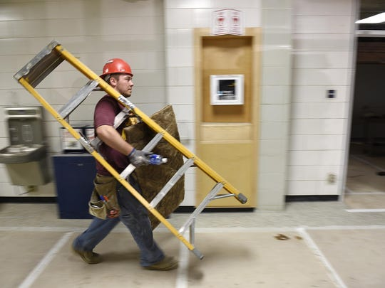 Logan Reid, Diamond Energy Systems Inc., heads with latter in hand to the next classroom Wednesday to insulate ductwork as construction continues at North Junior High School.