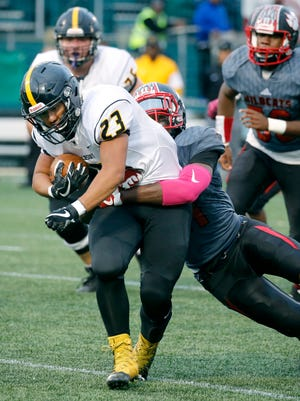 McQuaid's Mike Vongphachanh holds onto the ball while tackled by Wilson's Jervon Johnson in the first quarter at Capelli Sport Stadium