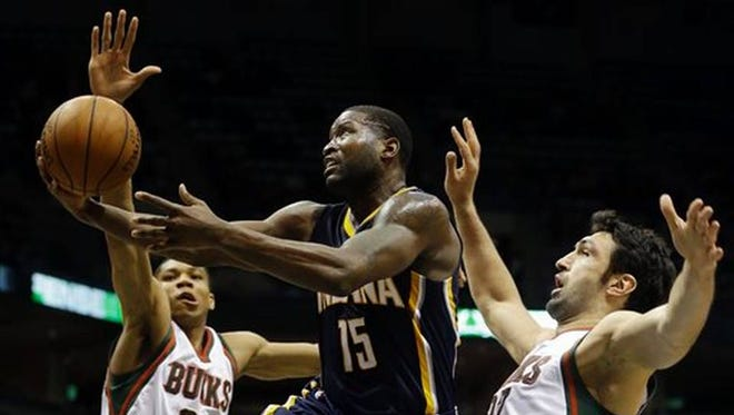 Donald Sloan drives to the rim in between two very large Bucks with active hands.
