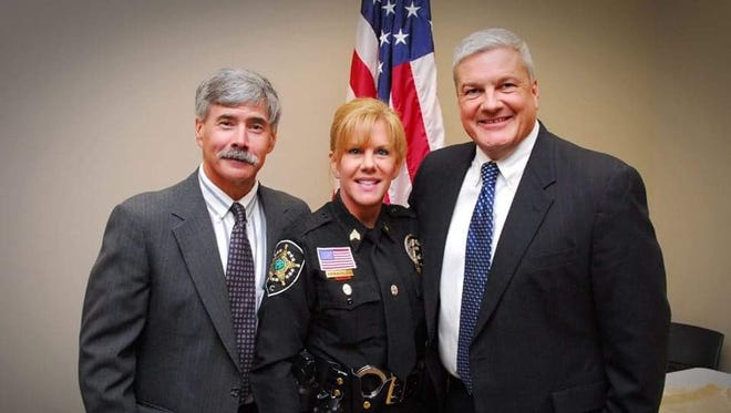 Robyn Michalove with her husband Roddy, far left, and Buncombe County Sheriff Van Duncan at her recent promotional ceremony.