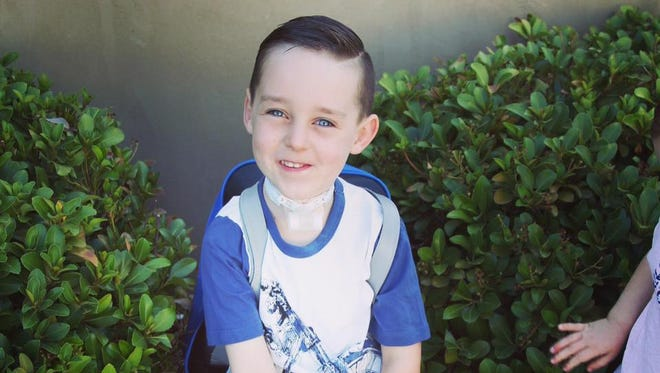 Lincoln Jensen sits outside waiting to attend his first day of school.