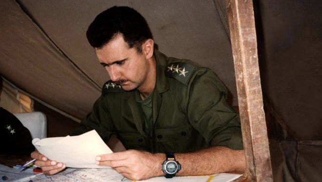 This 1994 photo posted on the official Facebook page of the Syrian Presidency, purports to show then-Captain Bashar Assad, looking at documents during a military project in Syria.