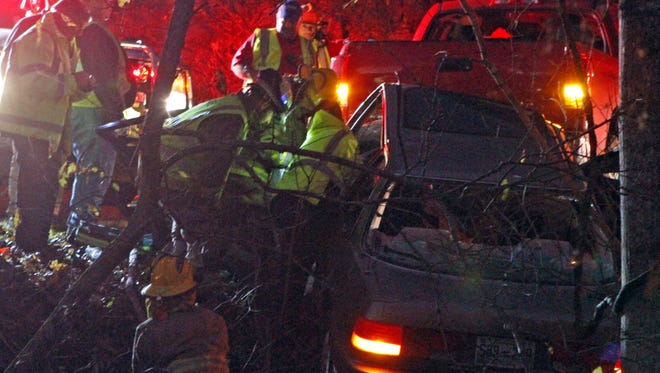 Rescuers work to save a woman as her car dangles 20 feet above a rushing creek Wednesday.