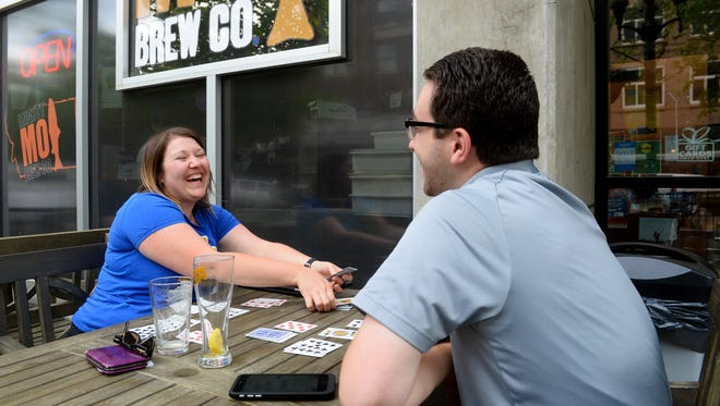 Andrea Hubbard picks up a pile of cards while playing Rummy with friend Kyler Baker on the Mighty Mo patio.