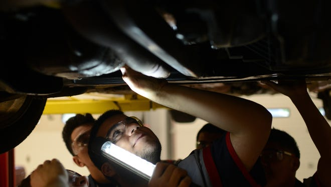 Raul Macias holds a light up while inspecting a 1999 Chrysler Sebring convertible  at City Stadium Automotive.