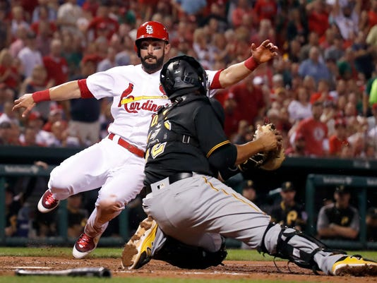 St. Louis Cardinals' Matt Carpenter, left, scores past Pittsburgh Pirates catcher Elias Diaz during the fifth inning of a baseball game Friday, Sept. 8, 2017, in St. Louis. (AP Photo/Jeff Roberson)