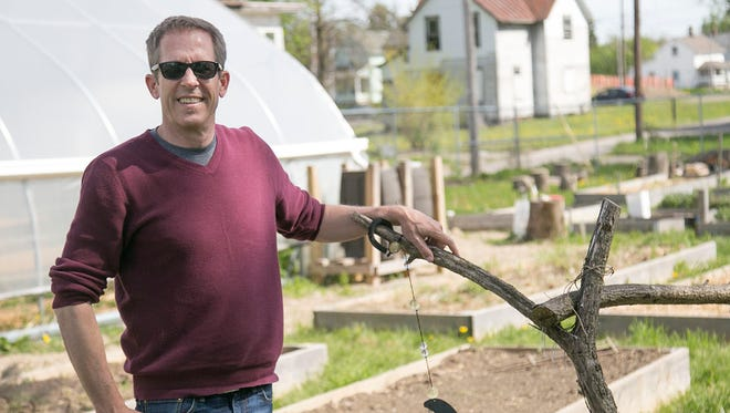 Kip Curtis, standing in the Blust Avenue Community Garden, is an assistant professor of history at the Ohio State University-Mansfield and an environmental historian.