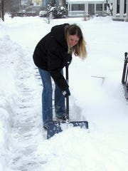 Janice Burrow-Goff shovels snow Wednesday from the