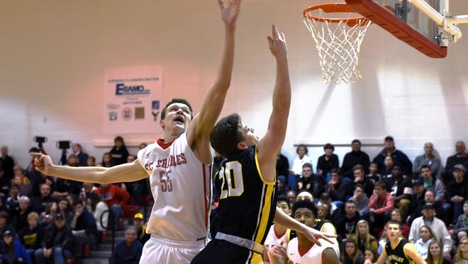 Tri-Valley's Caleb Craig is blocked by 6-foot-10 Nick Muszynski during the Scotties' 69-43 loss to Columbus St. Charles during the Division I central district tournament. Muszynski scored a game-high 30 points and grabbed 10 rebounds,