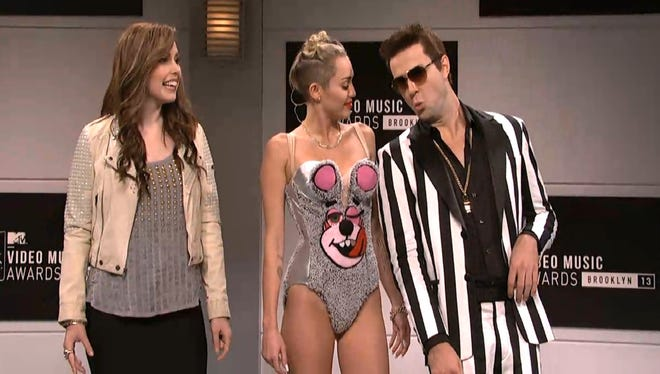 """Screen grab of opening skit from the Oct. 5, 2013, episode of NBC's 'Saturday Night Live,' featuring guest host and musical performer Miley Cyrus. Vanessa Bayer, left, played the """"old"""" Miley."""