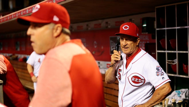Cincinnati Reds bench coach Jim Riggleman (35) passes the message on to Cincinnati Reds manager Bryan Price (38) to request a video review of the play at second base which was initially called safe in the top of the ninth inning.