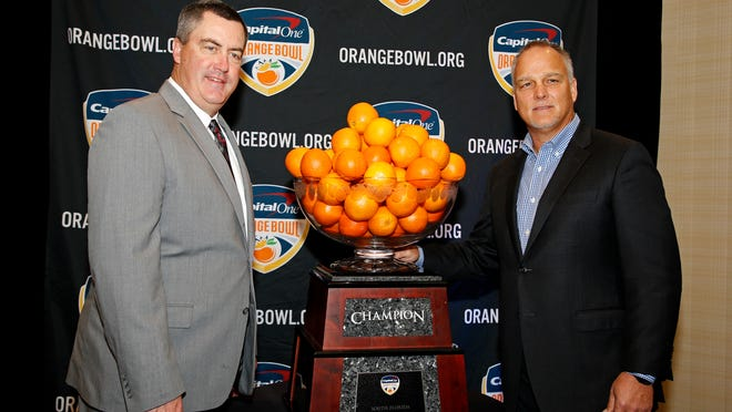 Wisconsin head coach Paul Chryst, left, and Miami head coach Mark Richt stand with the Orange Bowl trophy at an NCAA college football news conference in Fort Lauderdale, Fla., Friday, Dec. 29, 2017. The teams will meet in the Orange Bowl on Saturday, Dec. 30. (AP Photo/Joe Skipper)