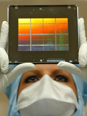 A technician wears an optical photomask for semiconductor production.
