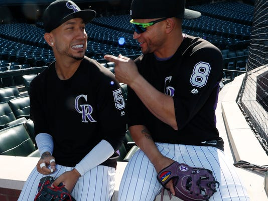 Colorado Rockies right fielder Carlos Gonzalez, left, jokes with left fielder Gerardo Parra as they warm up before a baseball game against the Los Angeles Dodgers, Friday, Sept. 29, 2017, in Denver. (AP Photo/David Zalubowski)