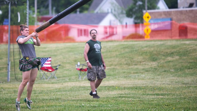 Katie Crowley throws a caber, a 14-foot long, 70-pound pole, during the Milwaukee Highland Games at Wauwatosa's Hart Park.