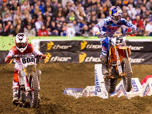 Ryan Dungey passes Mike Alessi for the lead, eventually winning the 450SX Main Event. Monster Energy AMA Supercross racing fans filled Lucas Oil Stadium, Saturday, March 1, 2014, as riders raced toward a FIM World Championship title.