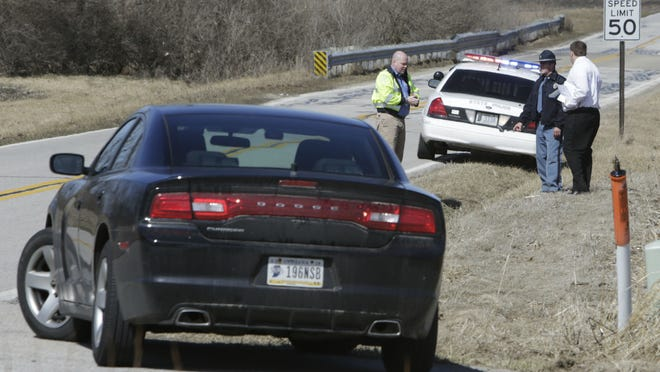 Indiana State Police detectives collect evidence from the roadside near County Roads 450 East and 550 South, along the route of a police chase that kept officers busy in two counties Tuesday, March 17.