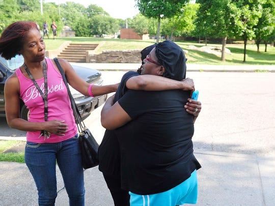 Family friend Vicki Jones, right, hugs Sharon Braden,