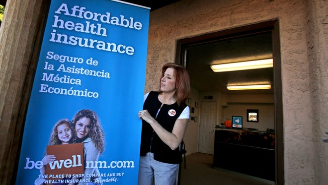 Enrollment counselor Ginger Lewis moves a banner outside the New Mexico Health Insurance Exchange's Farmington Enrollment and Assistance Center on late last year.